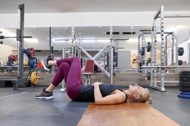 Jovem mulher loira desportiva, esticando o corpo enquanto fazia exercícios de ioga na academia