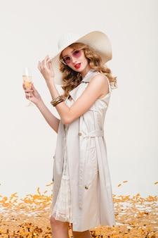 Jovem mulher loira elegante com um grande chapéu e óculos escuros segurando uma taça de champanhe em uma festa feliz