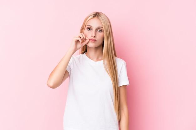Jovem mulher loira em fundo rosa com os dedos nos lábios, mantendo um segredo.