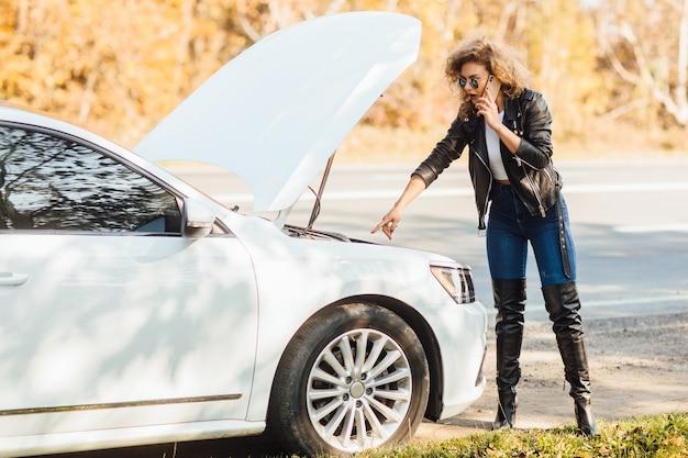 Jovem mulher loira em pé perto de um carro quebrado com capô estourado, falando em seu telefone celular enquanto espera por ajuda.