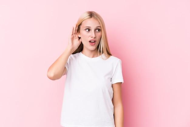 Jovem mulher loira em rosa tentando ouvir uma fofoca.