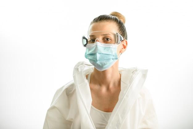 Jovem mulher loira em traje de proteção com óculos e máscara