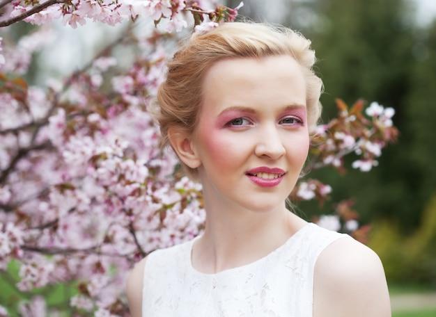 Jovem mulher loira em uma das flores de cerejeira rosa na primavera, close-up