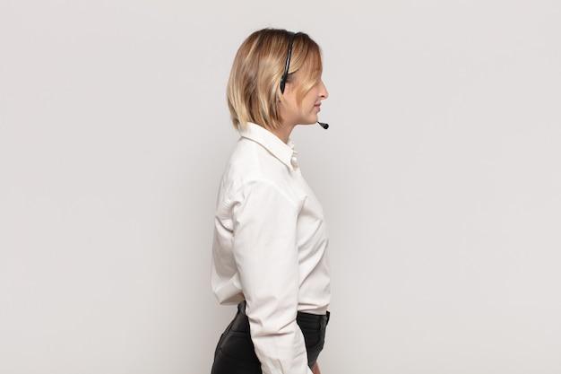 Jovem mulher loira em vista de perfil olhando para copiar o espaço à frente, pensando, imaginando ou sonhando acordada