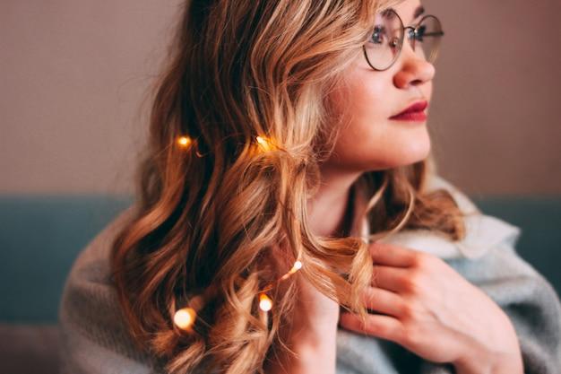 Jovem mulher loira encantadora em copos com luzes no cabelo