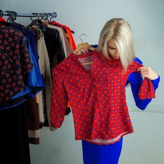 Jovem mulher loira escolhendo a camisa em loja de roupas. linda garota com muitas roupas. conceito de compras.