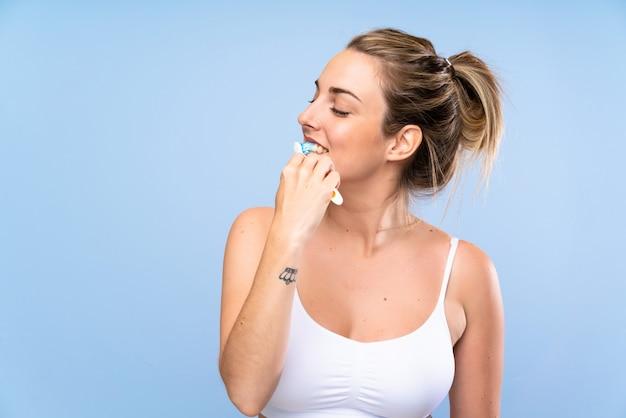 Jovem mulher loira escovando os dentes