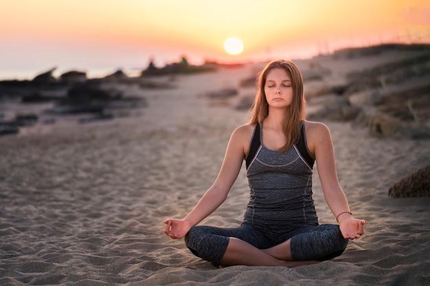 Jovem mulher loira está meditando à beira-mar em pose saudável na praia em raios de luz do sol, conceito de meditação yoga