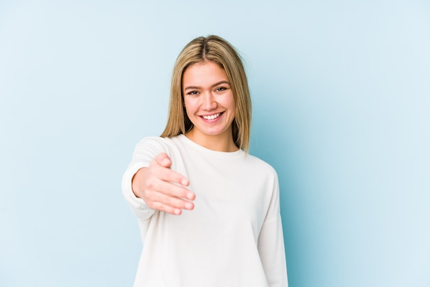 Jovem mulher loira, esticando a mão no gesto de saudação