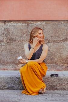 Jovem mulher loira falando com a localização do telefone na rua
