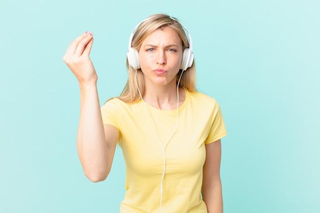 Jovem mulher loira fazendo capice ou gesto de dinheiro, dizendo para você pagar e ouvindo música.