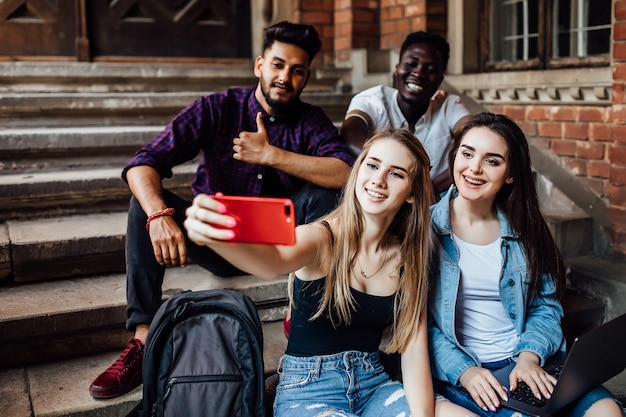 Jovem mulher loira fazendo selfie com os alunos de seus amigos, enquanto eles estão sentados na escada.