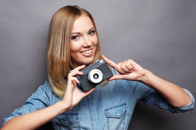 Jovem mulher loira feliz com câmera vintage