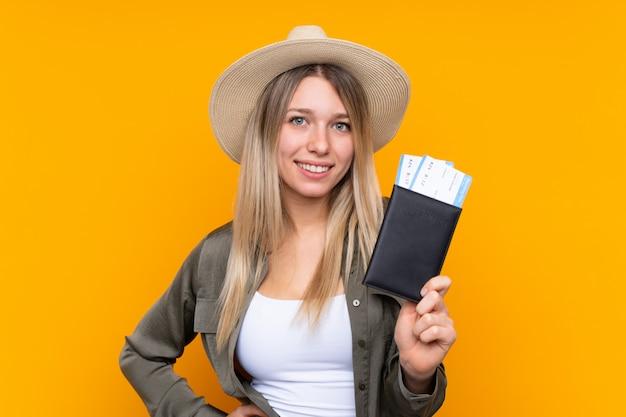 Jovem mulher loira feliz em férias com bilhetes de avião e passaporte