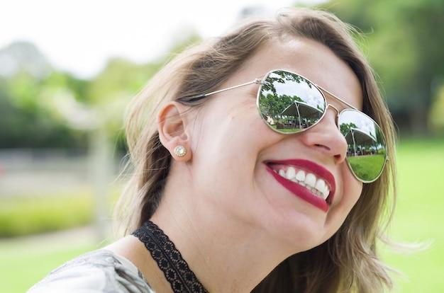 Jovem mulher loira feliz rindo no gramado.