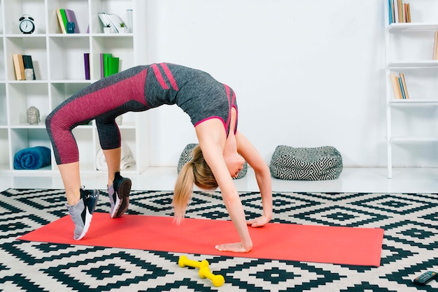 Jovem mulher loira fitness, estendendo-se na sala de estar