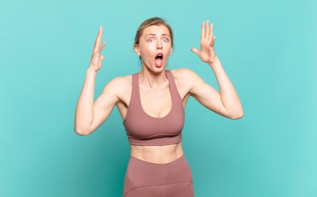 Jovem mulher loira gritando com as mãos no ar, sentindo-se furiosa, frustrada, estressada e chateada. conceito de esporte