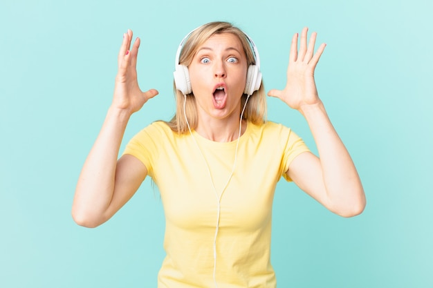 Jovem mulher loira gritando com as mãos para o alto e ouvindo música.