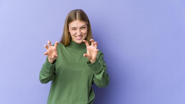 Jovem mulher loira isolada em um fundo roxo, mostrando garras imitando um gato, gesto agressivo.