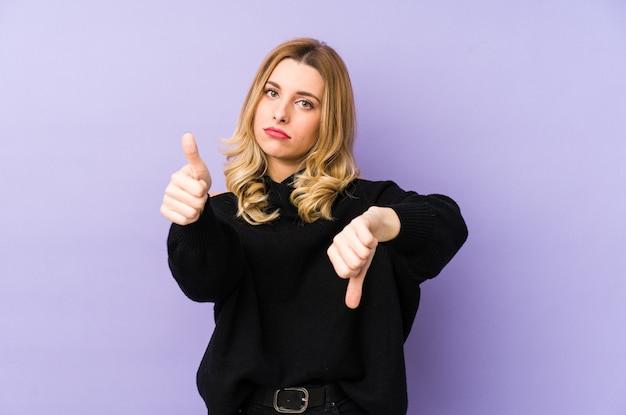 Jovem mulher loira isolada mostrando os polegares para cima e para baixo, difícil escolher o conceito