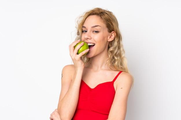 Jovem mulher loira isolada na parede branca, comendo uma maçã