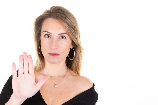 Jovem mulher loira isolada no branco fazendo o gesto de parada com a mão na palma da mão
