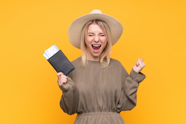Jovem mulher loira isolado parede amarela feliz em férias com bilhetes de avião e passaporte