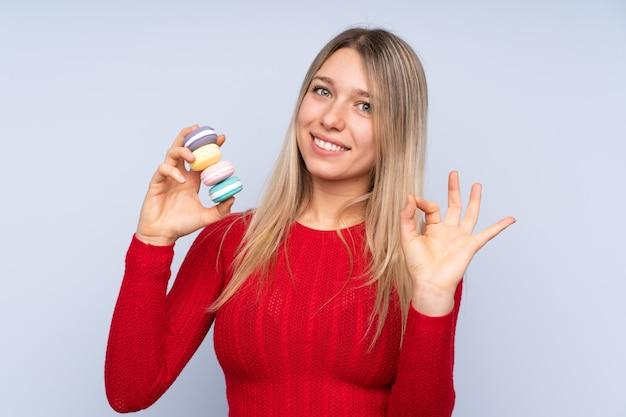 Jovem mulher loira isolado parede azul segurando macarons franceses coloridos e mostrando sinal de ok com os dedos