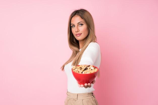 Jovem mulher loira isolado parede rosa segurando uma tigela de cereais