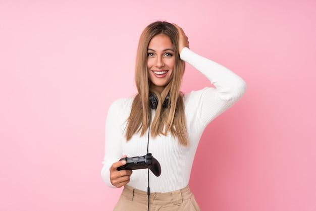 Jovem mulher loira isolado rosa jogando em videogame