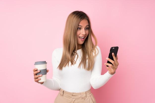 Jovem mulher loira isolado rosa segurando café para levar e um celular