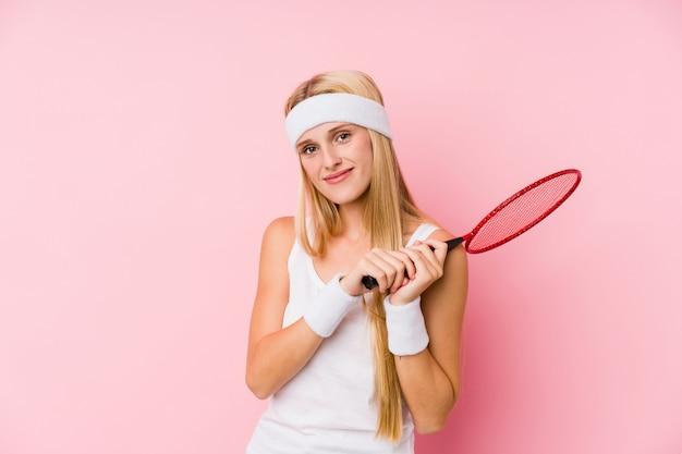 Jovem mulher loira jogando badminton isolado
