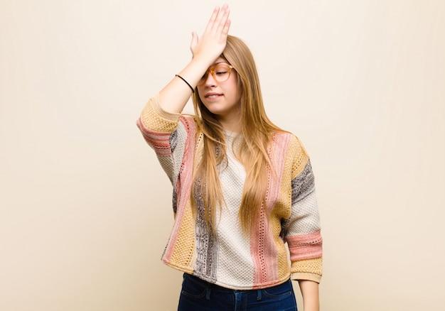 Jovem mulher loira levantando a palma da mão na testa pensando opa, depois de cometer um erro estúpido ou lembrar, sentindo-se burro contra parede bege