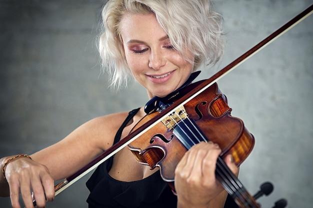 Jovem mulher loira linda com um vestido preto tocando violino no fundo da parede de tijolo branco.