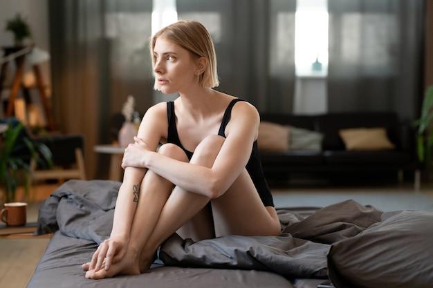 Jovem mulher loira linda em malha preta, com as pernas cruzadas enquanto está sentada na cama na manhã de sábado e pensando nos planos para o dia