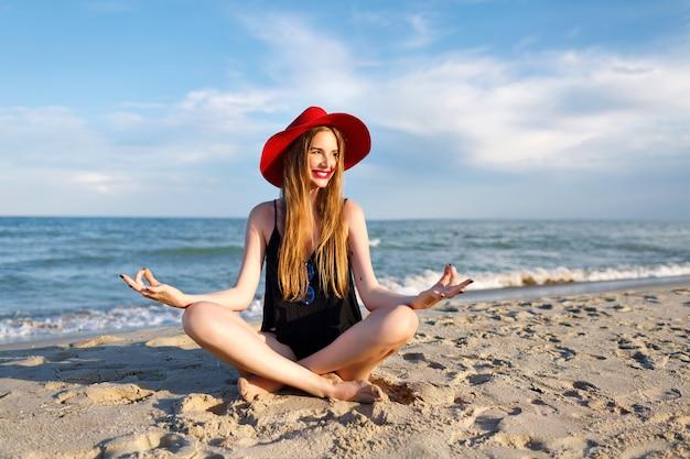 Jovem mulher loira meditar perto do oceano, férias de feijão, sol, usando chapéu vermelho e blusa, estilo de vida saudável, clima de ioga. sentado na areia e aproveite as férias.