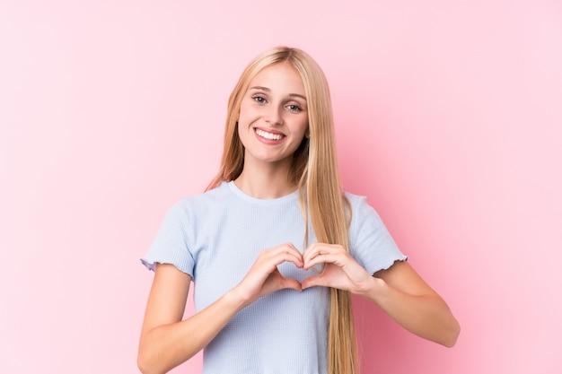 Jovem mulher loira na parede rosa, sorrindo e mostrando uma forma de coração com as mãos.