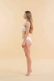 Jovem mulher loira na ponta dos pés, posando em roupa interior