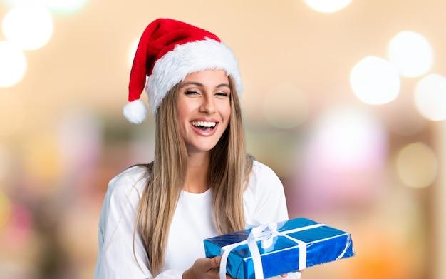 Jovem mulher loira nas férias de natal na parede sem foco
