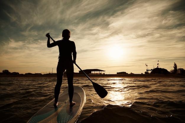 Jovem mulher loira no remo no mar