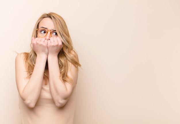 Jovem mulher loira olhando preocupado, ansioso, estressado e com medo, roer unhas e olhando para o espaço da cópia lateral na parede de cor lisa