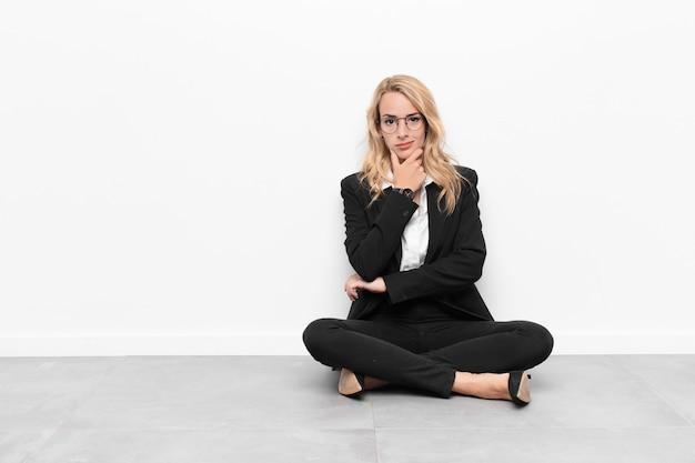 Jovem mulher loira olhando sério, confuso, incerto e pensativo, duvidando entre opções ou escolhas, sentado no chão