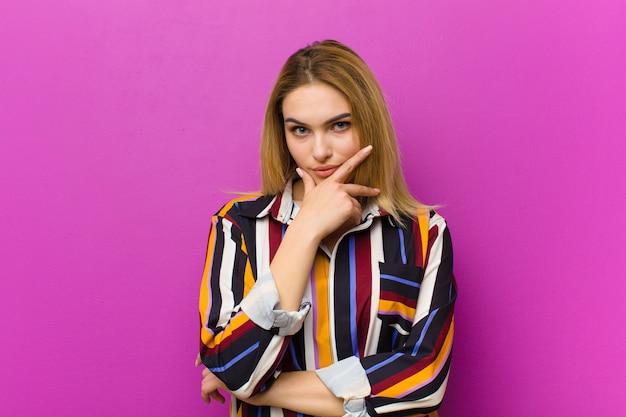 Jovem mulher loira olhando sério, pensativo e desconfiado, com um braço cruzado e mão no queixo, opções de ponderação contra parede roxa