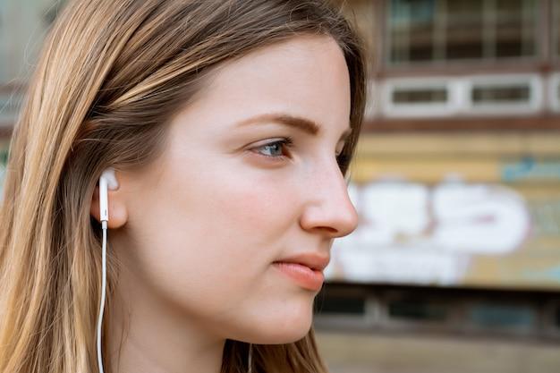 Jovem mulher loira ouvindo música com fones de ouvido