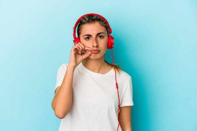 Jovem mulher loira ouvindo música em fones de ouvido isolados em um fundo azul com os dedos nos lábios, mantendo um segredo.