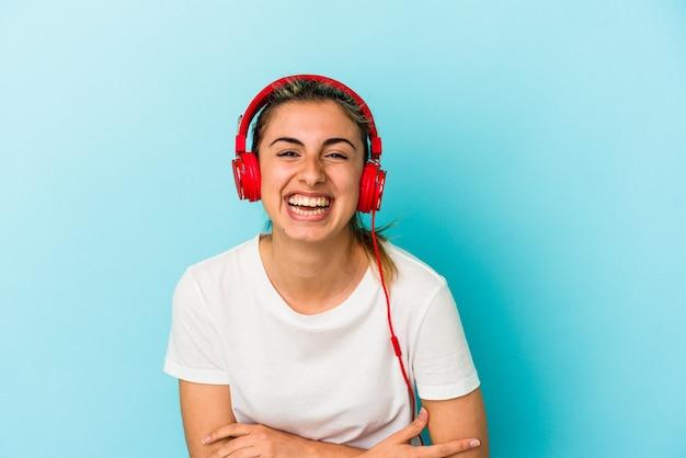 Jovem mulher loira ouvindo música em fones de ouvido isolados em um fundo azul, rindo e se divertindo.