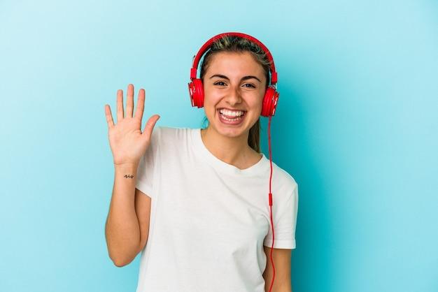 Jovem mulher loira ouvindo música em fones de ouvido isolados em um fundo azul, sorrindo alegre mostrando o número cinco com os dedos.