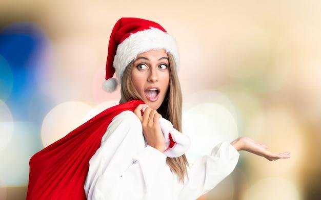 Jovem mulher loira pegando um saco cheio de presentes nas férias de natal na parede fora de foco