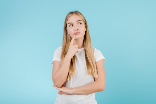 Jovem mulher loira pensando isolado sobre azul