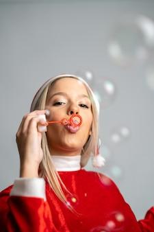 Jovem mulher loira posando com uma fantasia de miss papai noel e soprando bolhas